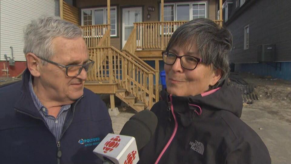 Deux personnes en entrevue devant une maison.