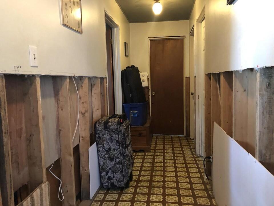 un corridor avec des murs éventrés , des boîtes et une valise