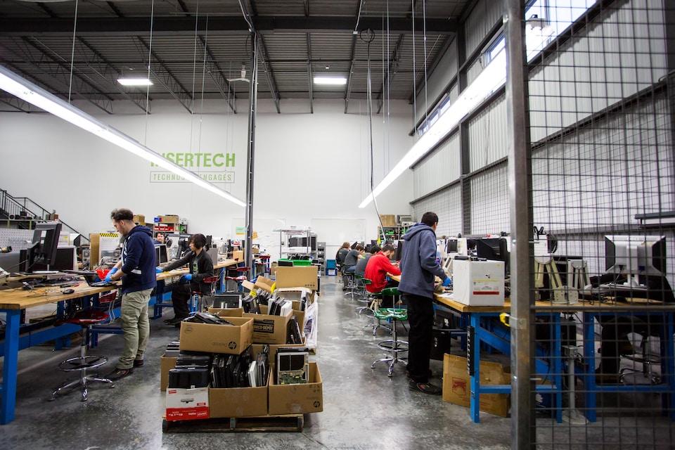 Des employés d'Insertech Angus sont alignés sur des tables de travail, dans l'entrepôt de l'entreprise d'économie sociale.