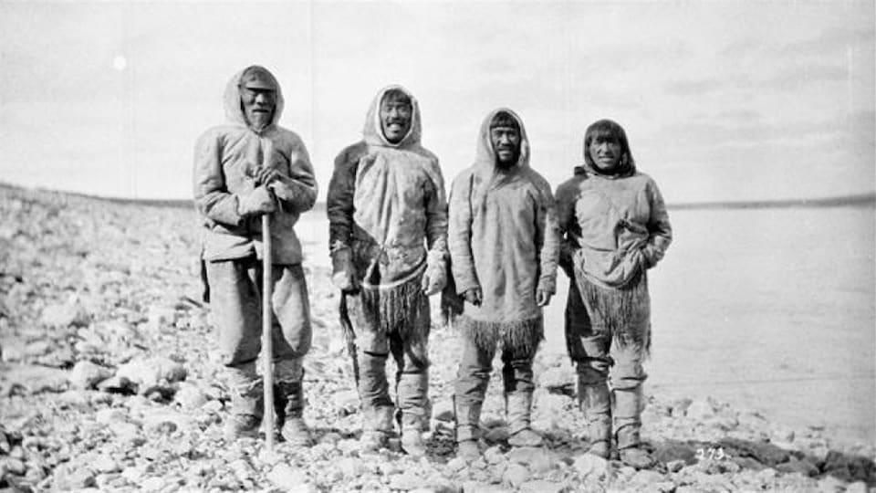 Ces quatre Inuits, debout près du rivage à Baker Lake (Qamanittuaq), au Nunavut, n'ont toujours pas été identifiés.