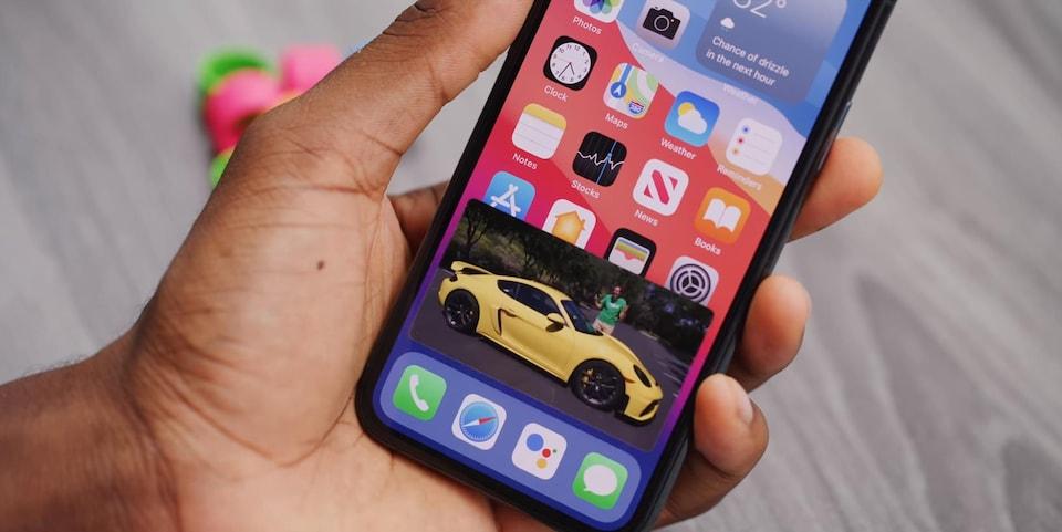 Un iPhone qui affiche une vidéo dans une petite fenêtre sur l'écran d'accueil.