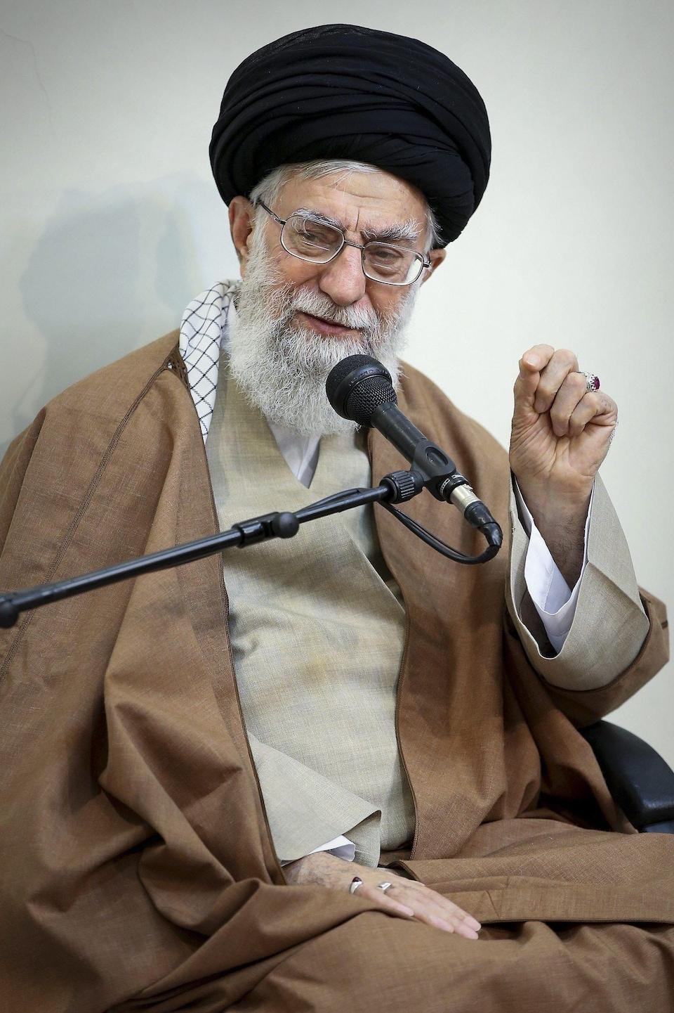 Plan rapproché de l'ayatollah Khamenei qui parle dans un micro en levant la main.