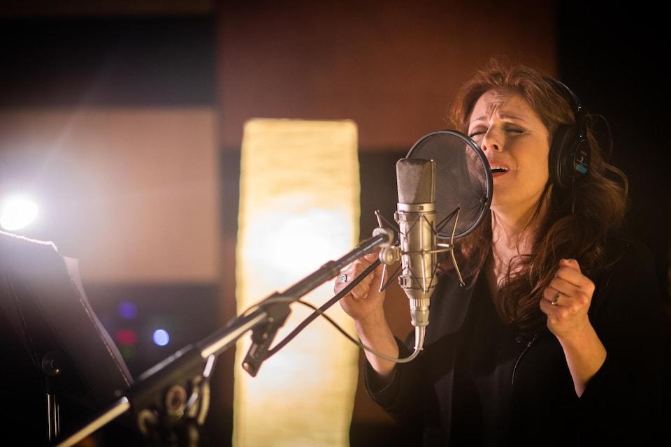 La chanteuse a les yeux fermés et chante devant un micro, une paire d'écouteurs sur les oreilles.