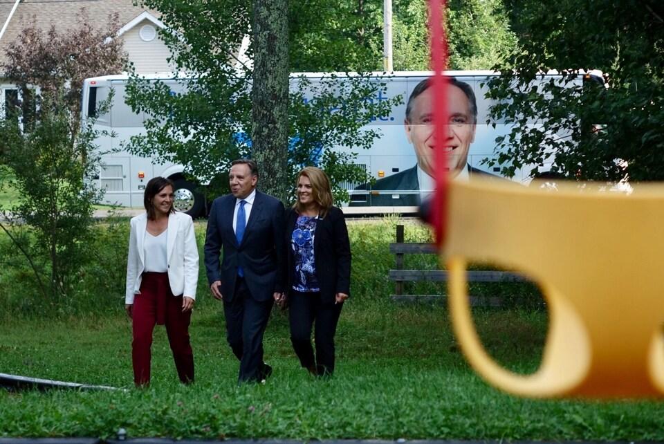 Les trois politiciens marchent dans un parc.