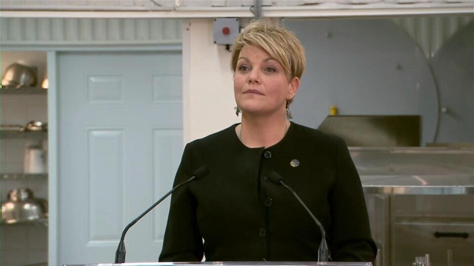 La ministre québécoise de l'Environnement, Isabelle Melançon, procédant à une annonce gouvernementale en direct des Ruchers Promiel, dans une salle qui s'apparente à un sous-sol.