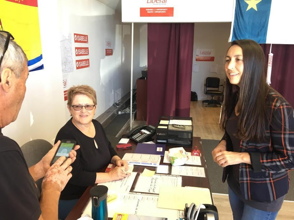 Isabelle Thériault avec des travailleurs de son parti dans son local de campagne.