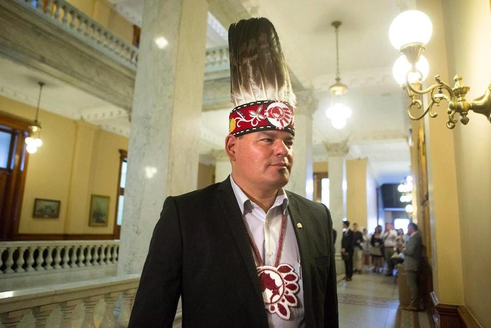 Photo d'un homme autochtone portant un couvre-chef avec des plumes