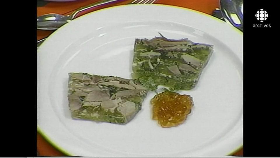 Deux tranches d'un mélange de morceaux de porc et de persil en gelée servie avec une garniture proche de la marmelade dans une assiette ronde classique.