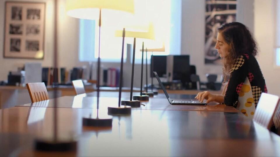 On voit la Dre Jabado en train de consulter son ordinateur, assise.