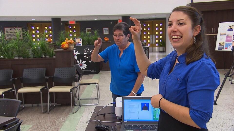 Deux femmes font des signes avec leur main pour les aînés suivant la formation pour apprendre le langage des signes québécois.
