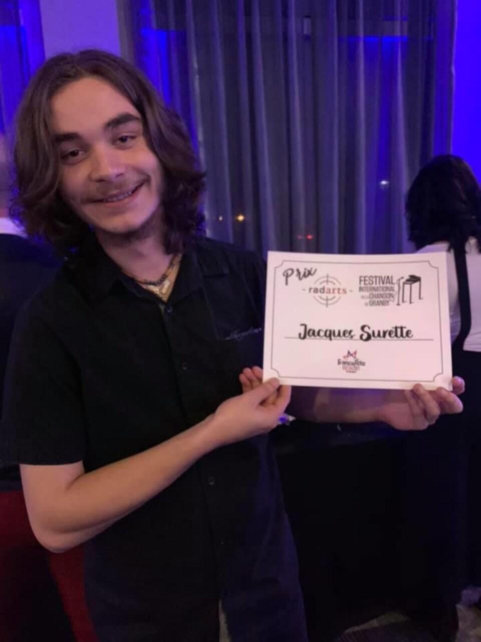 Jacques surette tenant un certificat sur lequel est écrit son nom.