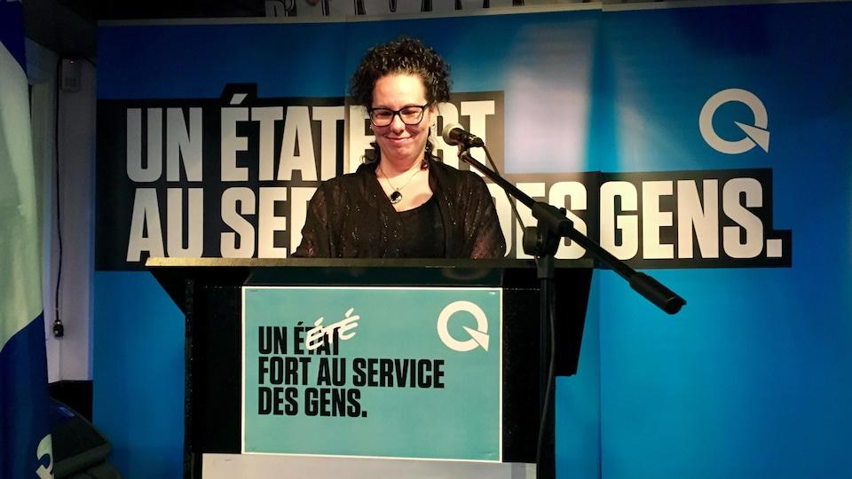 Jacynthe Bruneau, au podium, devant un micro, avec un bannière du Parti québécois
