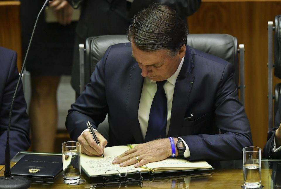 Jair Bolsonaro signe un document.