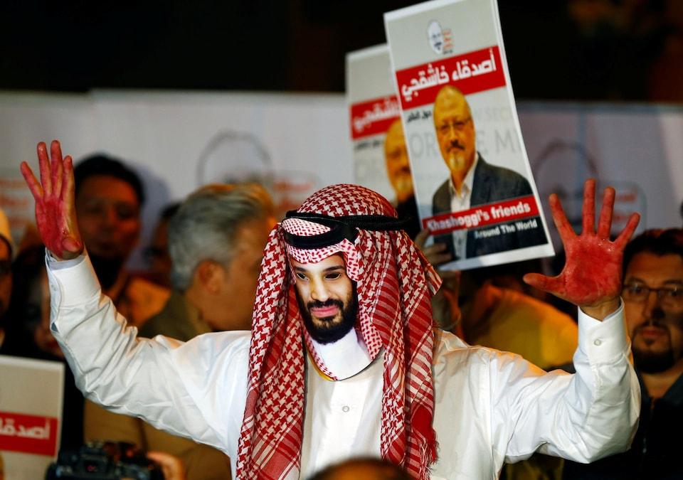 Un homme portant un masque de Mohammed ben Salmane lève ses deux mains peintes en rouge. Derrière lui, des gens brandissent des pancartes de Jamal Khashoggi.