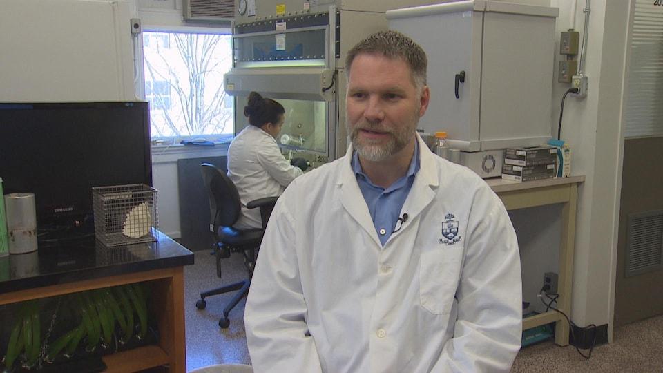 Homme en sarrau dans un laboratoire qui parle à la caméra.