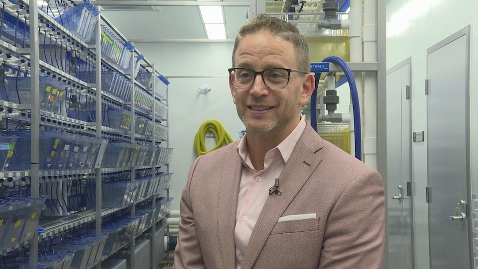 Jason Berman près d'une étagère d'aquariums dans son laboratoire.