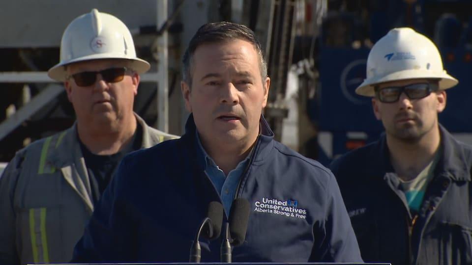 Jason Kenney en conférence de presse devant des travailleurs munis de casques.