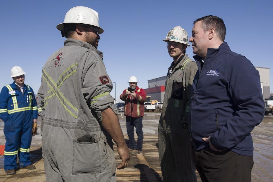 Jason Kenney parle à des travailleurs du secteur pétrolier.