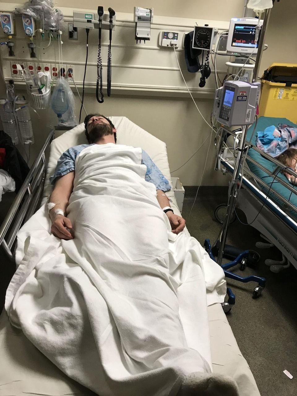 Un homme étendu sur un lit dans un hôpital.