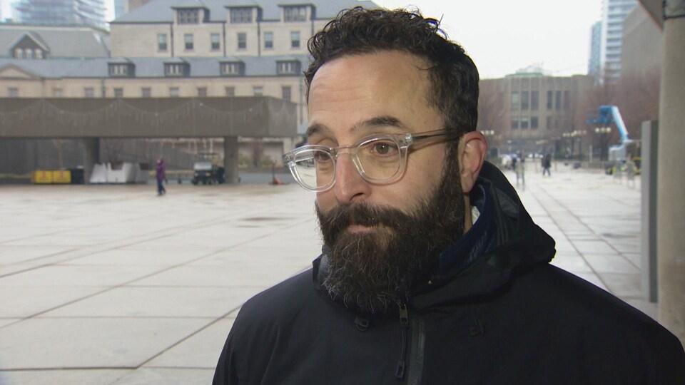 Un homme avec une barbe et des lunettes dehors