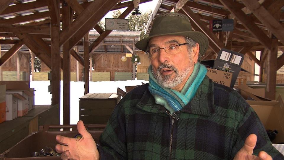 Un homme portant un chapeau, un manteau et un foulard gesticule avec ses bras en parlant avec un journaliste lors d'une entrevue à l'extérieur.