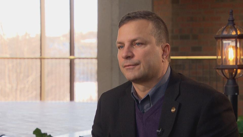 Un homme assis devant une lanterne lors d'une entrevue.