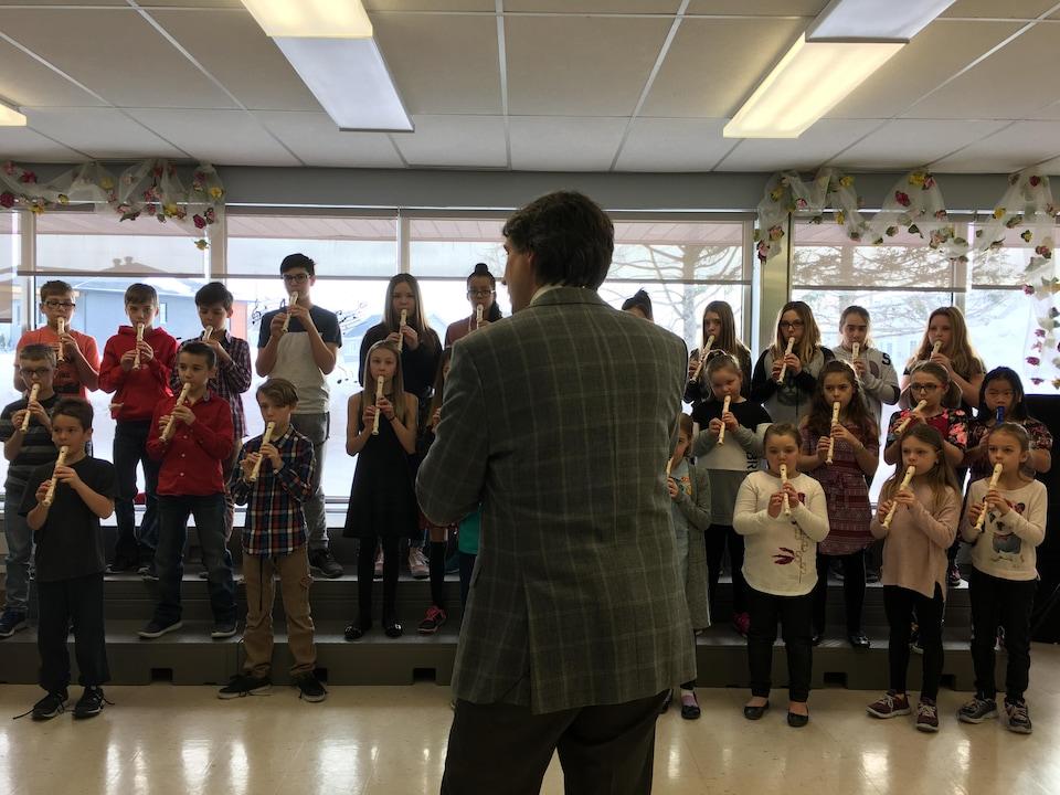 Jean-Michel Malouf devant les enfants qui jouent de la flûte à bec.