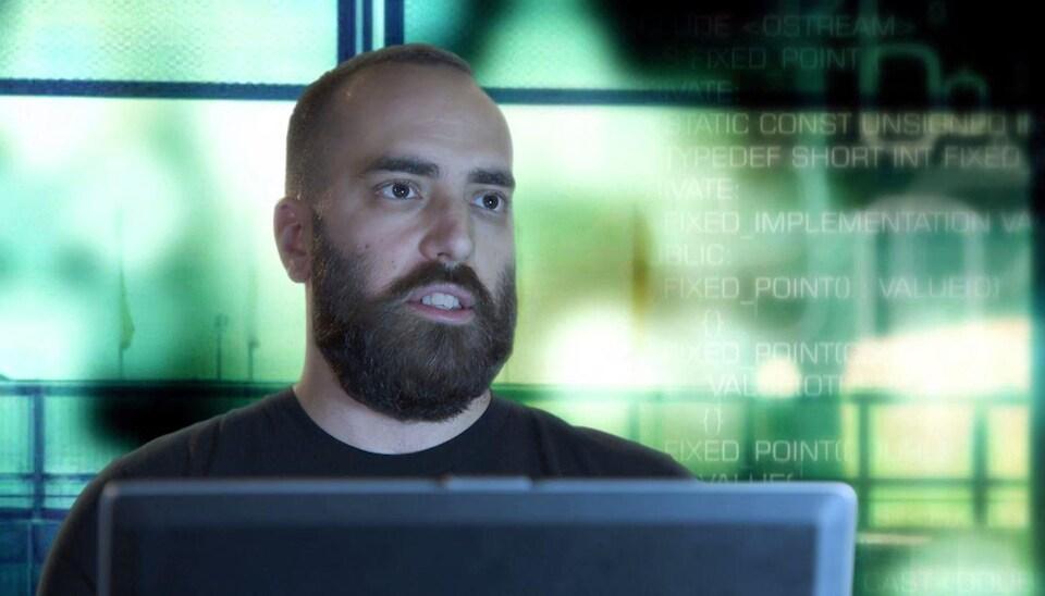 Le jeune homme est devant un écran d'ordinateur.