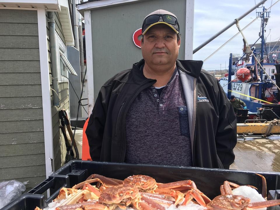 Le crabier Jean-Pierre Haché devant un panier de crabes.
