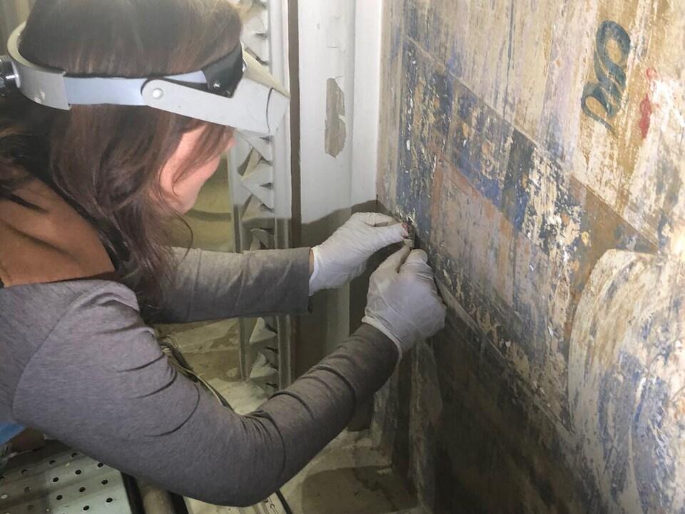 Jennifer Fotheringham gratte la peinture blanche sur le mur avec un petit scalpel.