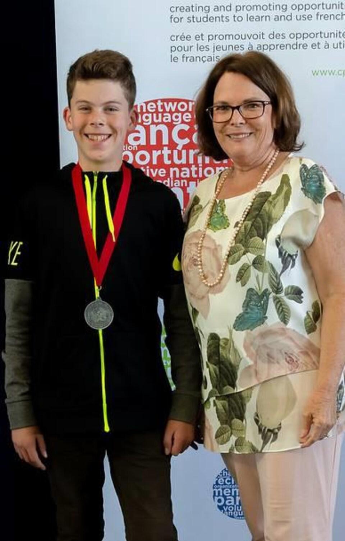 Le jeune Simon Minkow pose fièrement à la caméra pour montrer sa médaille en compagnie de l'organisatrice d'un concours d'art oratoire.
