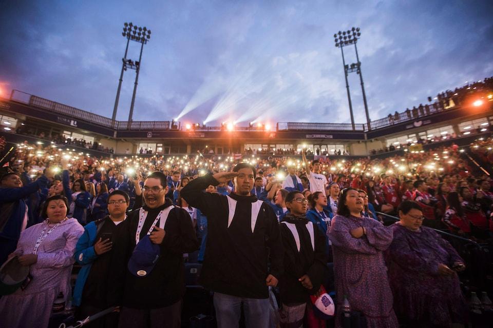 Des participants à la cérémonie d'ouverture des Jeux autochtones chantent et saluent l'Ô Canada.
