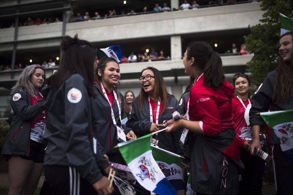 Groupe d'athlètes tenant des drapeaux du Yukon.