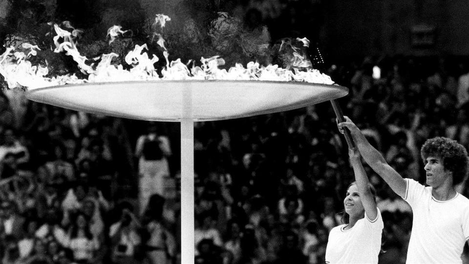 Stéphane Préfontaine et Sandra Henderson allument la vasque olympique au Stade lors de la cérémonie d'ouverture le 17 juillet 1976.