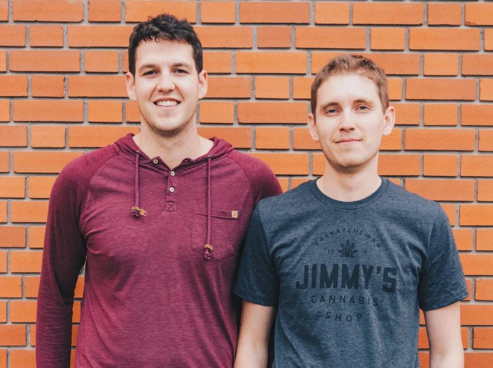 Deux hommes avec un mur de briques orangé derrière eux.