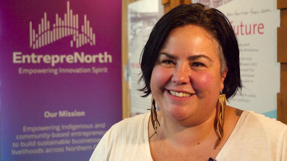 Une femme souriante devant une affiche de l'initiative EntrepreNorth.