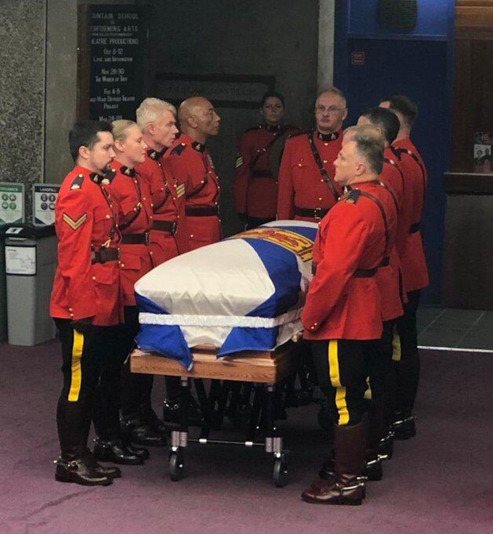 Des membres de la Gendarmerie royale du Canada en uniforme autour du cercueil.