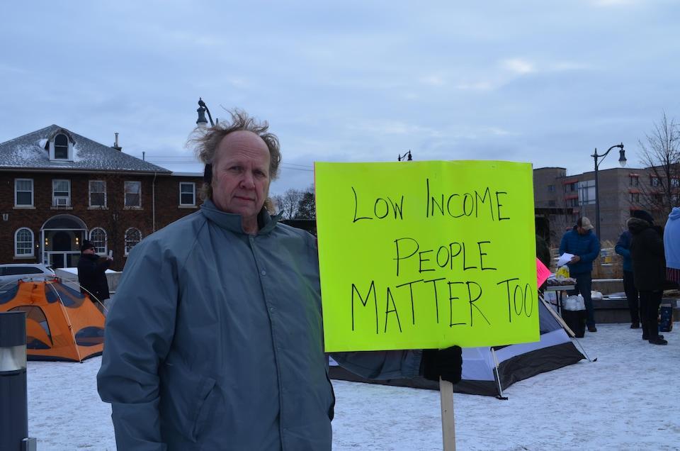 Un homme tenant une pancarte sur laquelle il est écrit en anglais «Les personnes à faible revenu compte aussi».