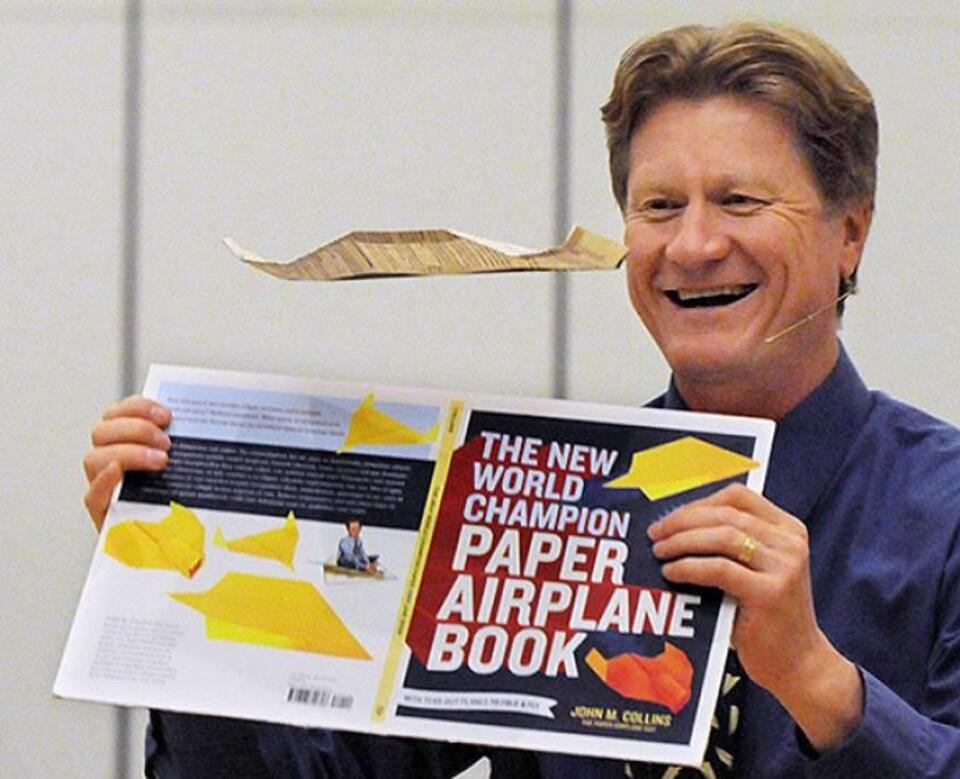 Un homme tient le livre The New world champion paper airplane book dans ses mains.