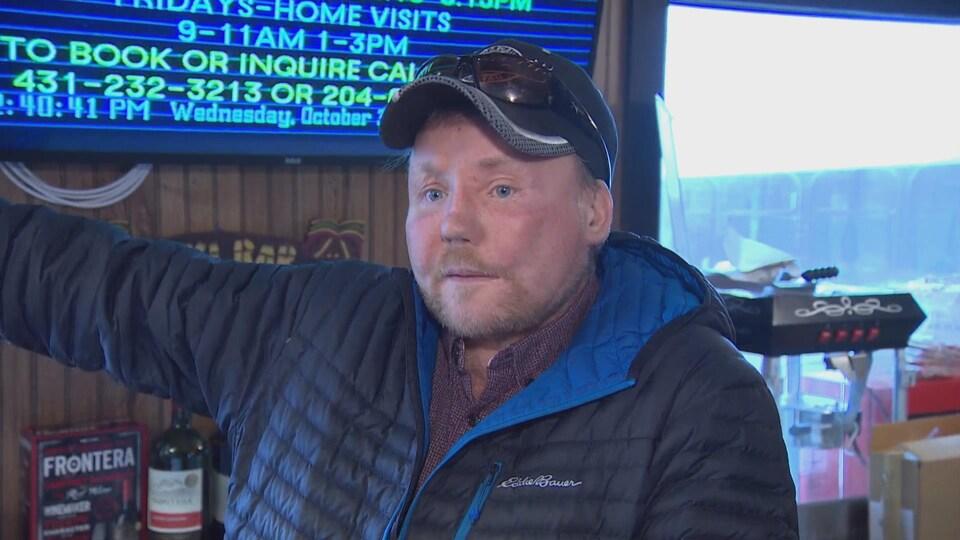 Derrière son comtoir, un homme avec une casquette et un manteau parle à la caméra en soulevant son bras droit, comme pour montrer quelque chose de l'autre côté.