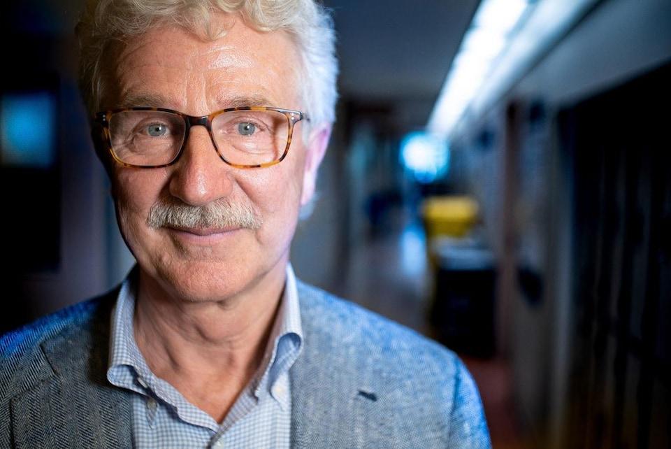 Un homme aux cheveux gris, à la moustache finement taillée et aux yeux bleus vifs, portant des lunettes.