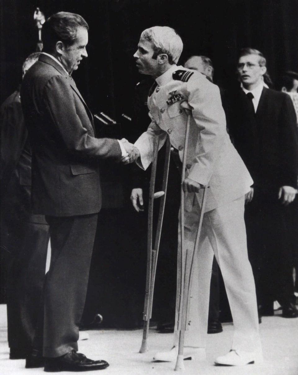 John McCain a des béquilles et serre la main du président américain de l'époque, Richard Nixon.