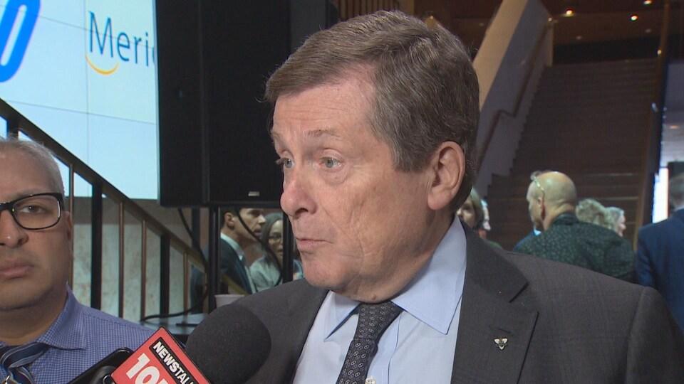 Un homme en complet gris devant un microphone.