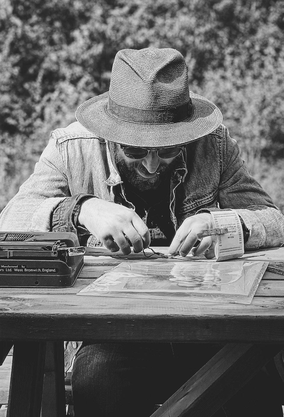 Photo en noir et blanc de Jonathan, portant un chapeau et des lunettes, assis à une table de pique-nique en train de coudre un livre à la main.
