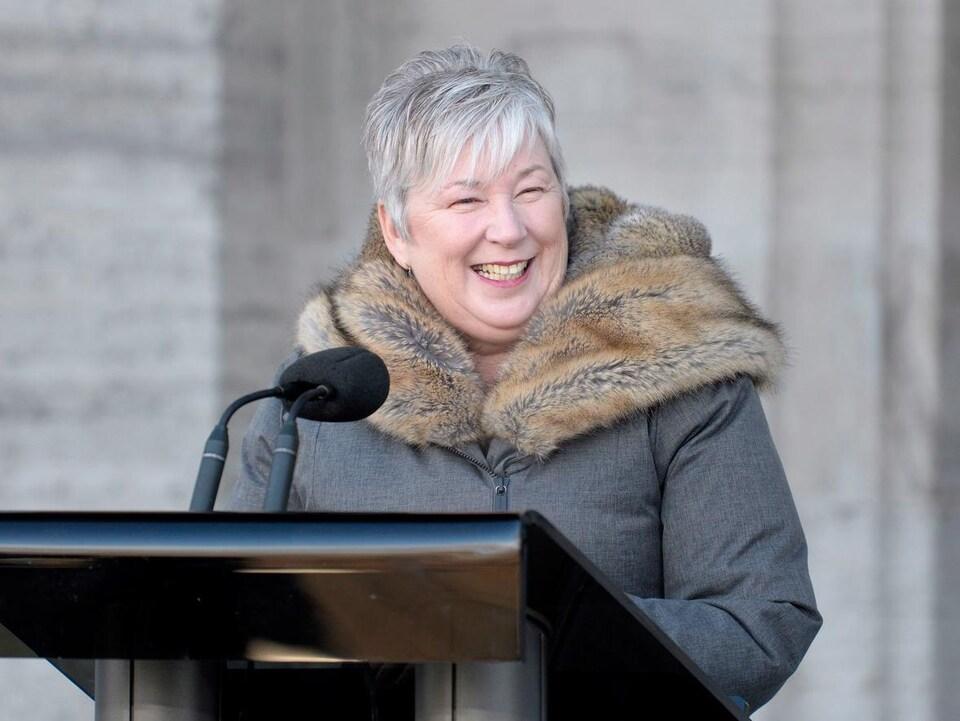 Bernadette Jordan, souriante, parle dans un micro installé devant l'édifice