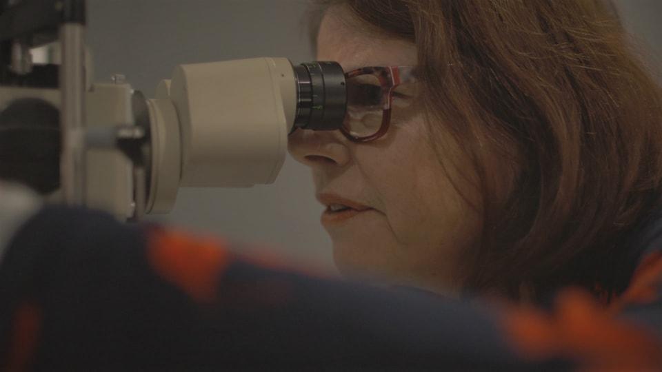 Josée Morin, de profil, en train de regarder dans un appareil d'optométrie.