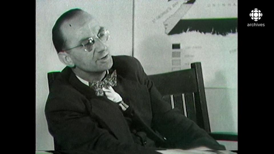 Joseph Smallwood en entrevue, avec un bout d'une carte géographique de Terre-Neuve en arrière-plan.