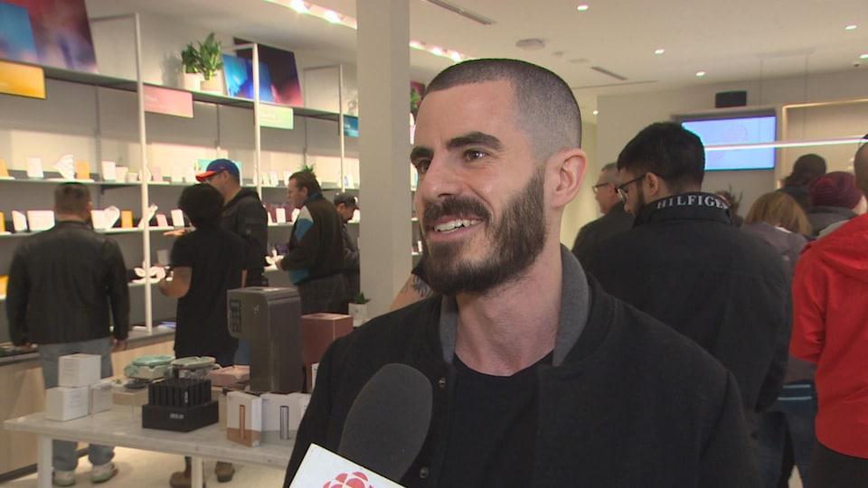 Un jeune homme aux cheveux noirs rasés et avec une barbe sourit au micro du journaliste, dans un magasin de cannabis.
