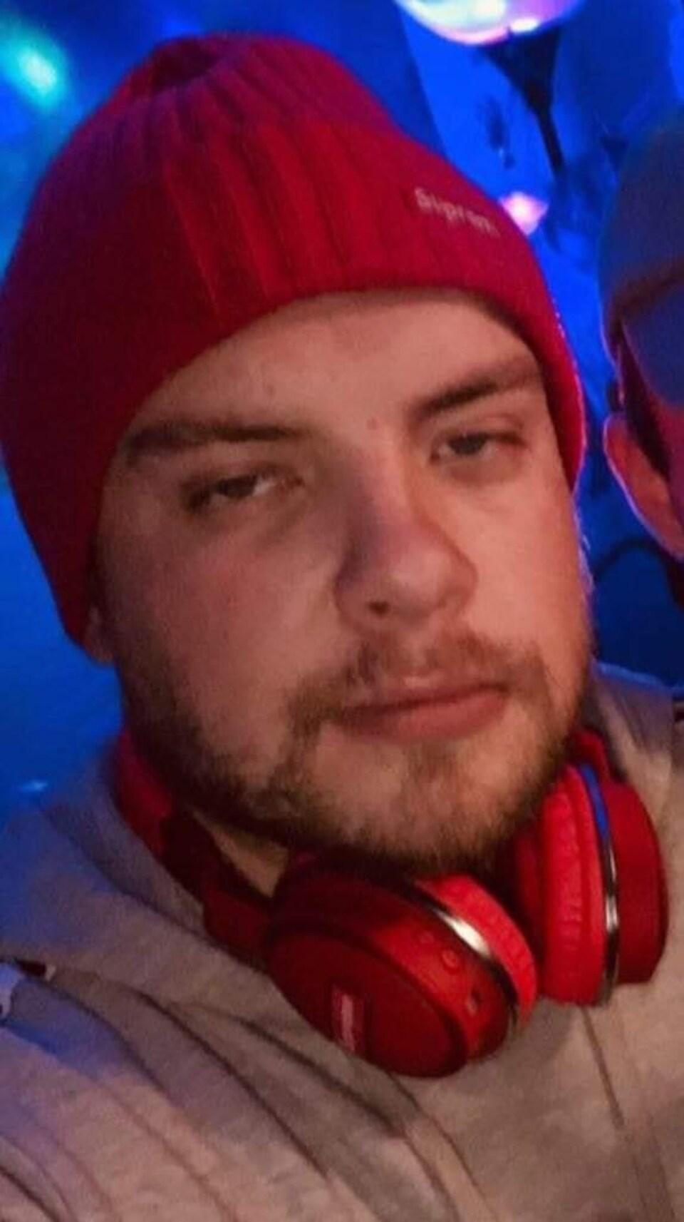 Un homme coiffé d'une tuque rouge et avec un casque d'écoute rouge autour du cou.