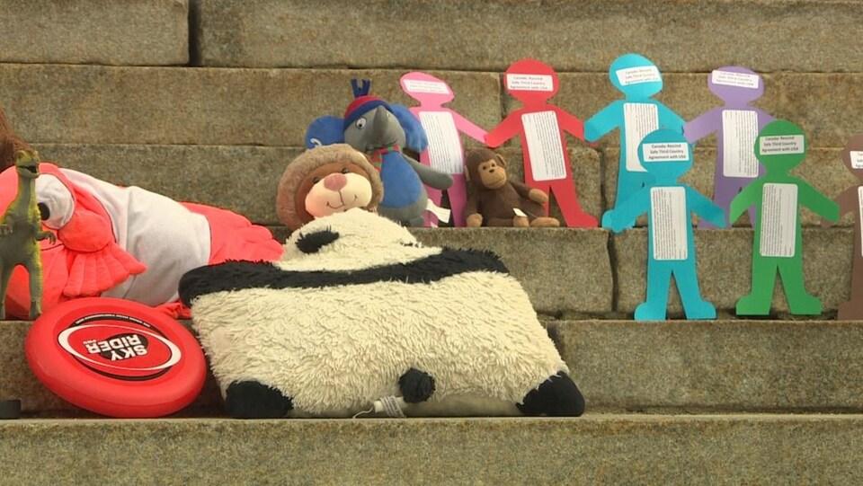 Sur des marches en béton, on voit des petites peluches en forme d'animaux et des papiers de différentes couleurs, découpés en forme de bonhommes qui se tiennent la main.